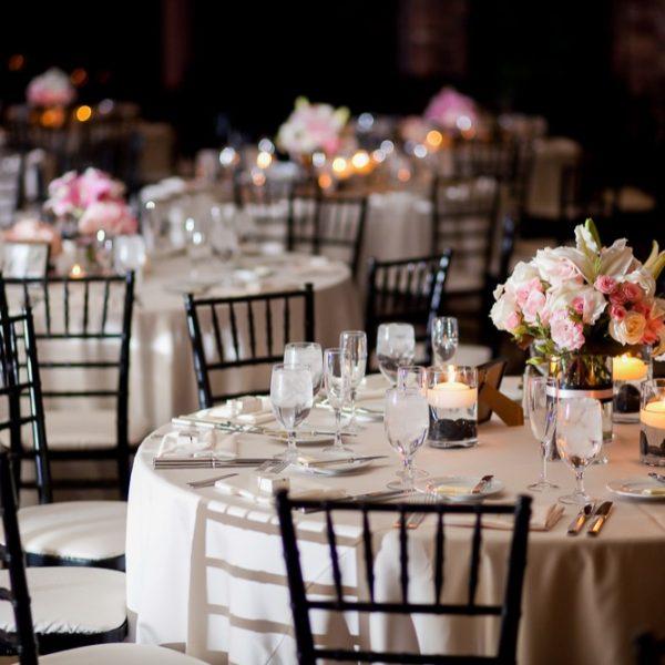 Multiple tables with centerpieces at an indoor elegant wedding reception