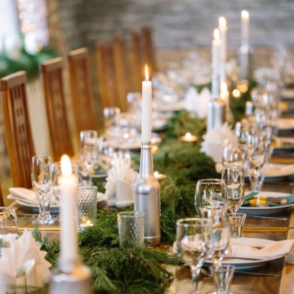 nature, winter, table setting concept. among clean plates, sparkling glasses, candle holders and other silverware there is lots of fresh and aromatic branches of some fur tree
